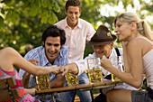 Cheerful people playing game in beer garden, fingerhakeln, Munich, Bavaria
