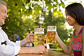 Older Bavarian man and asian woman toasting each other, Munich, Bavaria