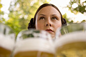 Waitress with beer steins in beer garden, Munich, Bavaria
