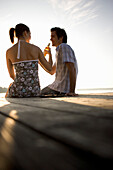 Two people sitting on boardwalk drinking beer and looking at sunset, Munich, Bavaria