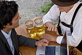 Young business man and older Bavarian man in beer garden, Munich, Bavaria