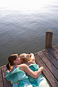 Two girls lying on jetty, Starnberger See, Bavaria, Germany