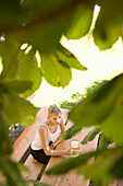 Young woman sitting at bench in beer garden, reading a book, Munich, Bavaria