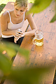 Young woman waiting for someone in beergarden, Bavaria, Germany