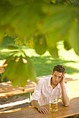 Young man waiting for someone in beergarden, Bavaria, Germany