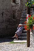 Elderly lady sitting on a step, Ticino, Switzerland