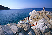 People sitting on stones at the beach of Marciana Marina, Elba, Tuscany, Italy, Europe