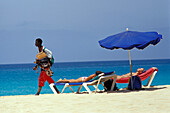 Women lying on deck chairs under sunshade, Beach of Santa Maria, Sal, Cape Verde Islands, Africa