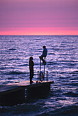 Two teenager talking on jetty, Havsbad, Baltic Sea. Visby, Gotland, Sweden