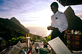 Laughing waiter standing on the terrace of Restaurant Dasheene, Ladera Resort, Soufrière, St. Lucia, Carribean