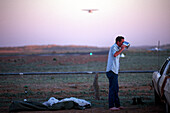 Junger Mann trinkt morgens Tee vor der Startbahn des Birdsville Airport, Birdsville, Simpson Desert, Australien