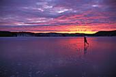 Woman skating on ice, lake in Vastergotland, Sweden