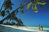 Young couple on an idyllic palm beach under blue sky, Zanzibar, Tanzania, Africa
