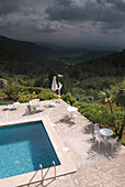 Pool of the Hotel Posada del Marques with view at scenesy and thunder clouds, Majorca, Spain