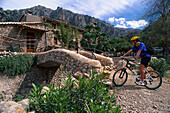 Man on mountain bike in front of Finca Baltix d`Avall, Tramuntana, Majorca, Spain, Europe