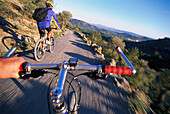 Two men riding bicycle, view from bicycle behind, road near Castell Alaro, Tramuntana, Majorca, Spain