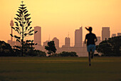 Jogger in a park at sunset, Downtown, Sydney, New South Wales, Australia