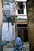 Man driving a moped through an alley, Old Town,  Zanzibar, Tanzania, Africa