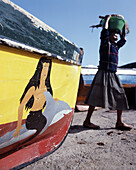 Local woman carrying fish in a basket, Fishing boat with painting of a mermaid, Ponta do Sol, Santo Antao, Cape Verde