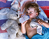 Child lying on blanket, drinking from baby bottle, Dueodde, Bornholm, Baltic Sea, Denmark