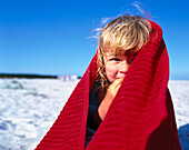 Girl 2-3 Years, on beach wrapped in red towel, Dueodde, Bornholm, Baltic Sea, Denmark