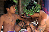 A man wearing a headdress tatooing a boy at Tiki village, Moorea, French Polynesia, Oceania