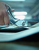 Cutting jeans fabric with a pair of scissors, Italy