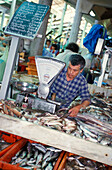 Vendor at a fish stand at the market hall, Loulé, Faro, Algarve, Portugal, Europe
