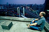 Meditation auf Hausdach, Stadtautobahn, Roppongi Tokyo, Japan
