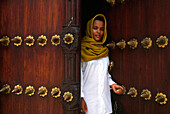 Moslem woman standing at an old door, Stone Town, Zanzibar City, Zanzbar, Tanzania