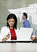 Businesswoman using a laptop, holding a mobile phone, Vienna, Austria