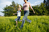 Women with boy running in nature, Women with boy running in nature, Mother with son running through meadow, People Lifestyle Nature Family