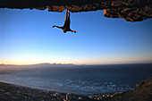 Rock climber hanging upside down, Muizenberg Bay, South Africa