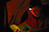 Woman reading a book with a flashlight, torch, Camping, South Africa
