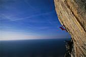 Male free climber scaling rock face, No Siesta 8b, Muzzerone, Portovenere, Cinque Terre, Liguria, Italy