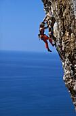 Female free climber scaling rock face, Muzzerone, Portovenere, Cinque Terre, Liguria, Italy