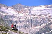 Woman and dog having a rest, hiking on Tauerngold Hiking Trail, Rauris, Hohe Tauern, Salzburger Land, Austria