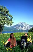 Girls having a rest in a field of flowers, Traun Lake, Traunstein Mountains, Salzkammergut, Austria