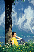 Woman relaxing under tree at Traunsee, Salzkammergut, Austria