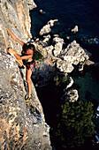 Woman climbing Evanjelium 5b, Cliffbase, Hvar, Croatia