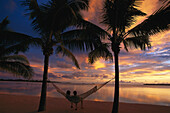 Couple relaxing in a hammock at sunset, Aitutaki Lagoon Resort, Cook Islands, South Pacific