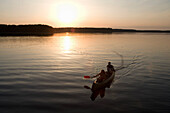 Couple canoeing at sunset, Zotzensee, Mecklenburgian Lake District, Germany