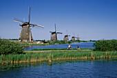 Windmuehlen und Radfahrer, bei Kinderdijk Niederlande