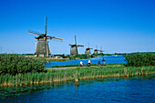 Windmills in a row, People on a cycle tour, Kinderdijk, Netherlands