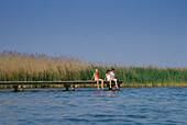 Tourists sitting on a boardwalk, Mueritz Lake, Mecklenburgian Lake District, Mecklenburg-Western Pomerania, Germany