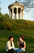 Young couple in front of Monopteros Pavillon in English Garden, Munich, Bavaria, Germany