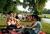 Young women in front of Eisbach, picnic, English Garden, Munich, Bavaria, Germany