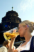 Girl in Dirndl dress drinking beer in beergarden, Chinesischer Turm, English Garden, Munich, Bavaria, Germany
