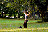 Woman exercising Tai Chi in Park next to Isar, Munich, Bavaria, Germany