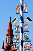 Maibaum, Maypole at the Viktualienmarkt with steeple in the background, Munich, Bavaria, Germany